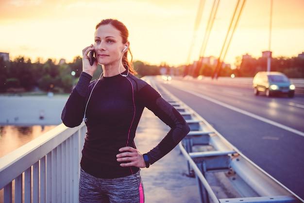 Fitness mujer hablando por teléfono inteligente
