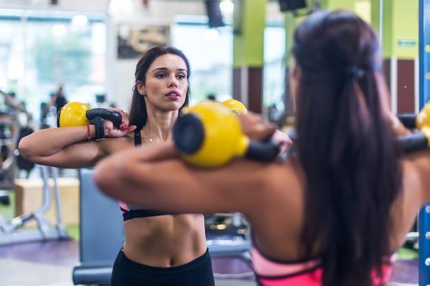 Fitness mujer haciendo ejercicio con una campana hervidor de agua