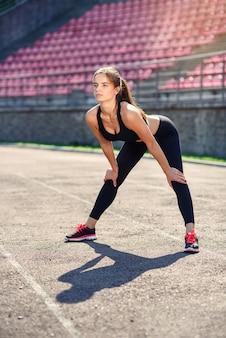 Fitness mujer haciendo estiramientos en el sadium antes de entrenar