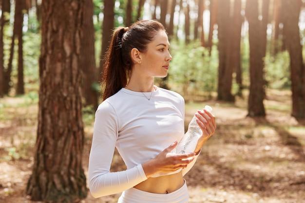 Fitness mujer hermosa con cabello oscuro y cola de caballo sosteniendo una botella de agua y mirando a otro lado, posando después de hacer ejercicio en el bosque