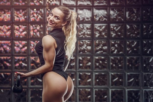 Fitness mujer inflar músculos entrenamiento en gimnasio