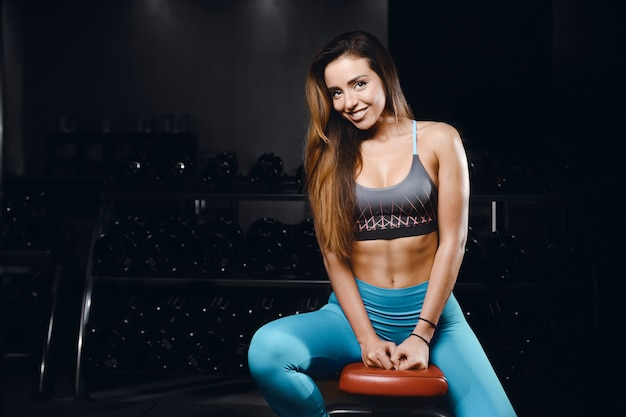 Fitness mujer inflar los músculos en el gimnasio