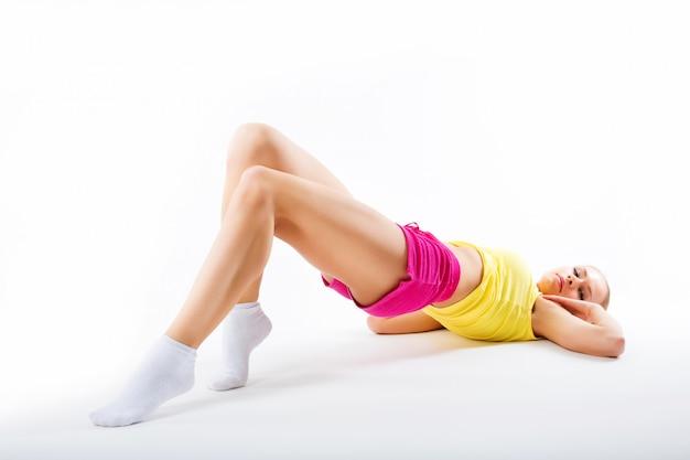 Fitness mujer joven se encuentra sobre un fondo blanco