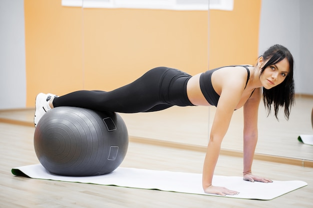 Fitness, mujer joven fitness con fitball gris, entrenamiento crossfit