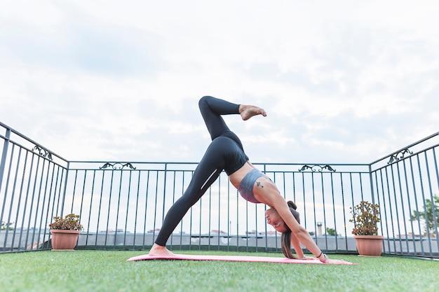 Fitness mujer joven haciendo ejercicio en balcón en césped