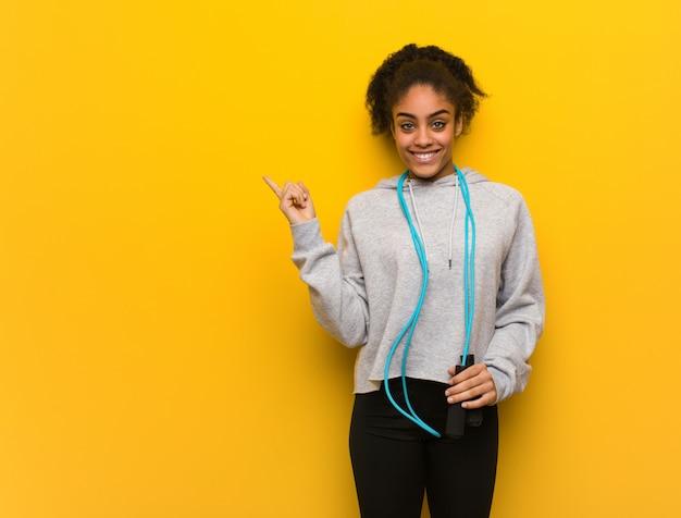 Fitness mujer joven negro apuntando hacia el lado con el dedo.