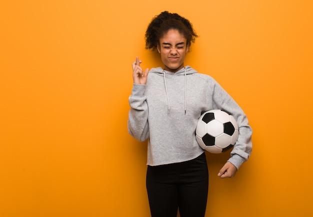 Fitness mujer joven negro cruzando los dedos para tener suerte. sosteniendo un balón de fútbol.