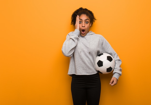 Fitness mujer joven negro sorprendido y conmocionado. sosteniendo un balón de fútbol.