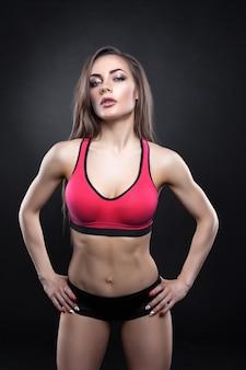 Fitness mujer joven posando y mirando