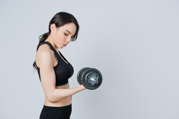 Fitness mujer levantando pesas, chica ejercicio en la mañana, entrenamiento