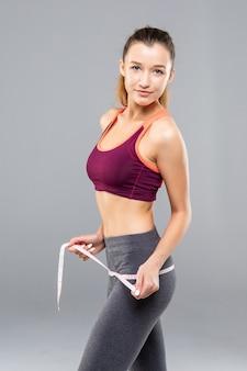 Fitness mujer midiendo su cuerpo aislado. conceptos de pérdida de peso