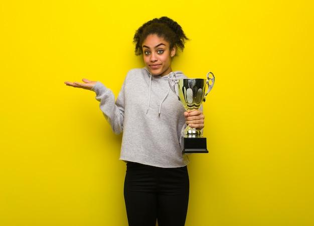 Fitness mujer negra joven dudando y encogiéndose de hombros. sosteniendo un trofeo.