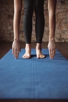Fitness mujer de pie descalzo y estiramiento sobre estera