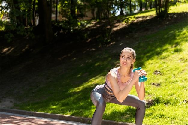 Fitness mujer se pone en cuclillas con pesas al aire libre