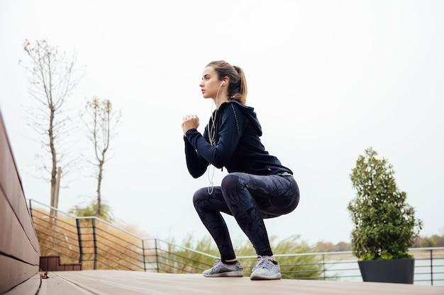 Fitness mujer saltando al aire libre en entorno urbano