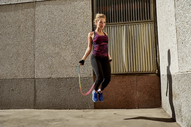 Fitness mujer saltando al aire libre en entorno urbano.