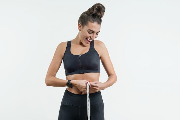 Fitness mujer sosteniendo una cinta de centímetro alrededor de su cintura.