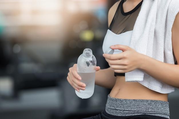 Fitness mujer sosteniendo la botella de agua potable.