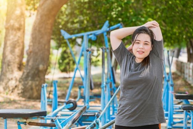 Fitness mujeres gordas tríceps estiramientos al aire libre en el parque. joven adolescente asiática ejercicio de calentamiento en la dieta de la mañana.