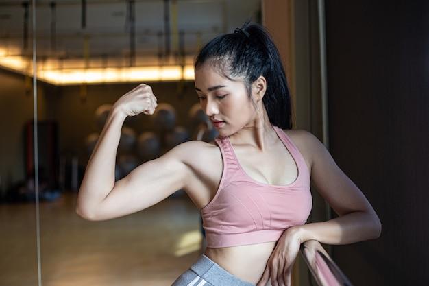 Fitness mujeres muestran los músculos del brazo en el gimnasio.