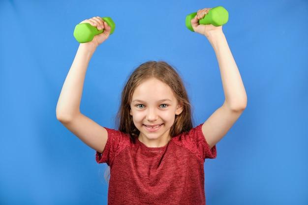 Fitness niño. retrato de una niña deportiva con pesas en un espacio azul