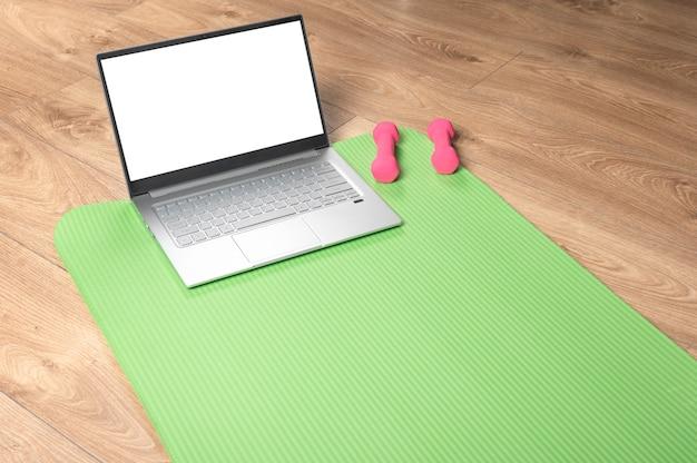Fitness yoga en línea, maqueta de portátil. mancuernas rosa, tapete de gimnasia y portátil gris sobre piso de madera. concepto de entrenamiento en línea.