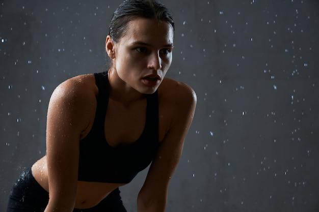 Fitnesswoman tomados de las manos sobre las rodillas bajo la lluvia
