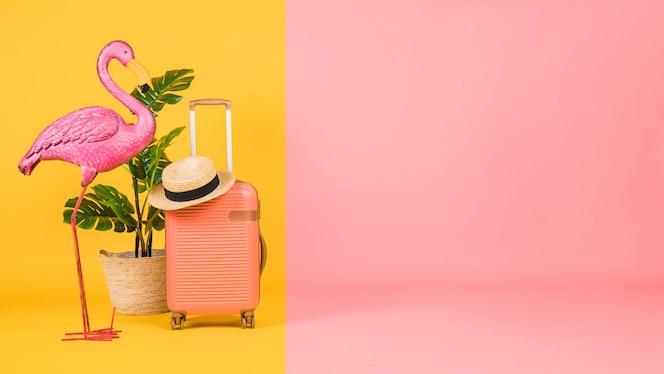 Flamenco, planta y maleta sobre fondo multicolor.
