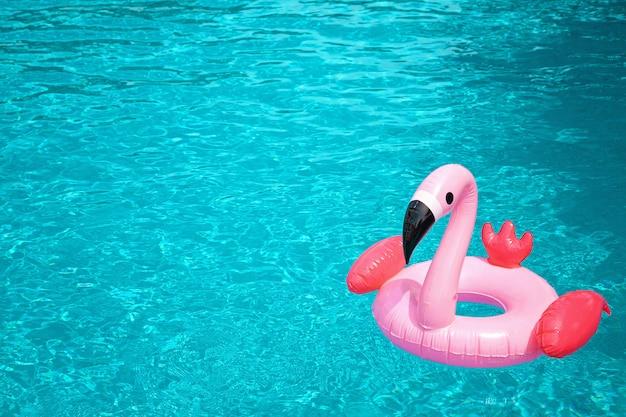 Flamenco rosado inflable en el agua azul de la piscina.