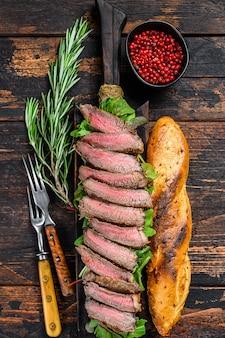 Flank steak sándwich de baguette con rúcula sobre una tabla para cortar