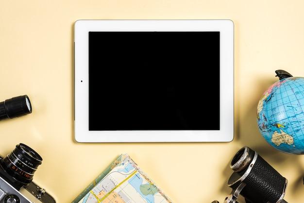 Flash; globo; mapa; binocular y cámara con tableta digital con pantalla negra.