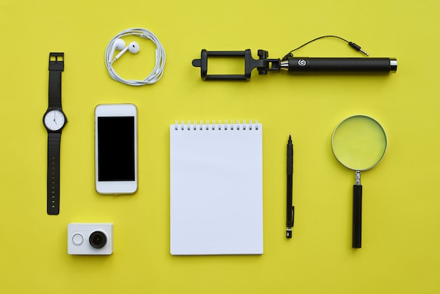 Flat lay de accesorios sobre fondo de escritorio amarillo