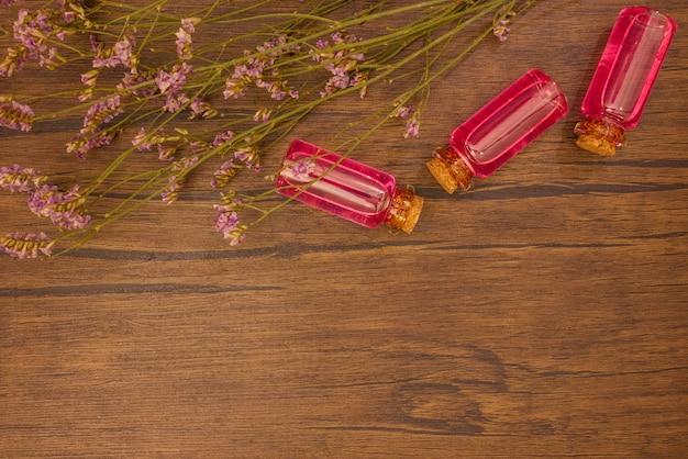 Flat lay aceites esenciales con extracto de flores sobre fondo de madera con espacio de copia
