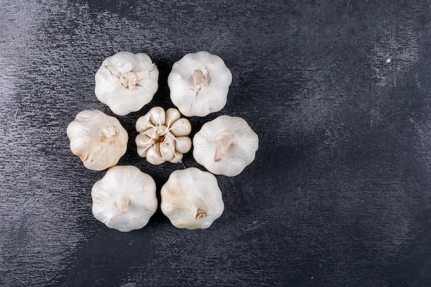 Flat lay ajo formando forma de flor en la mesa oscura