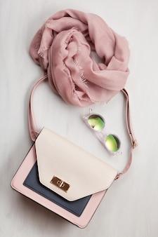 Flat lay con bolsa, bufanda rosa y gafas de sol.