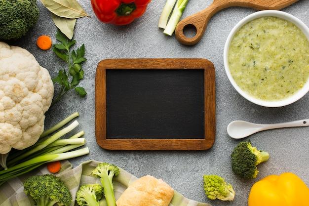Flat lay brócoli bisque y verduras con pizarra en blanco