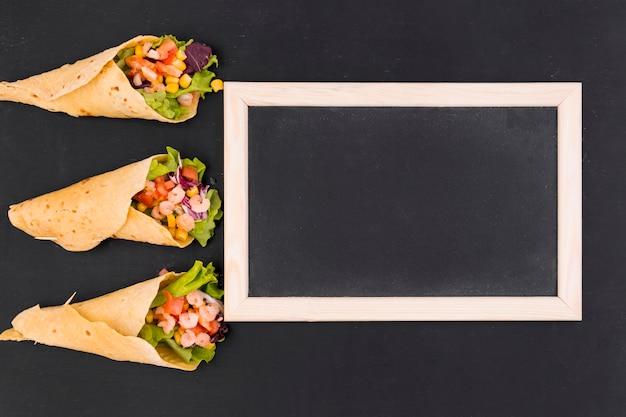Flat lay de burritos y pizarra