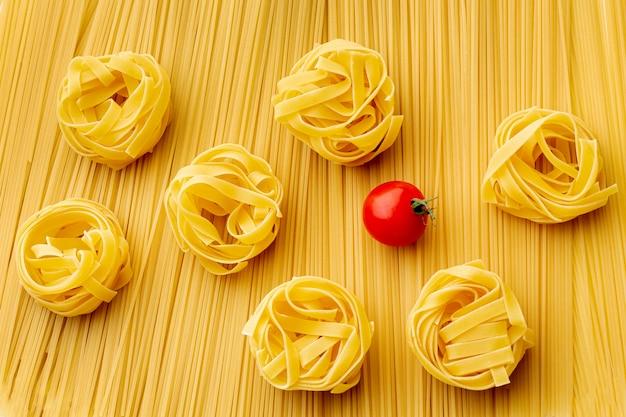 Flat lay sin cocer espaguetis tallarines y tomates
