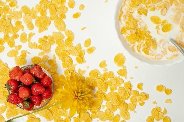 Flat lay copos de maíz con leche y fresas sobre fondo liso