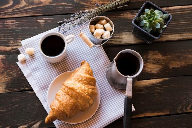 Flat lay delicioso café con croissant