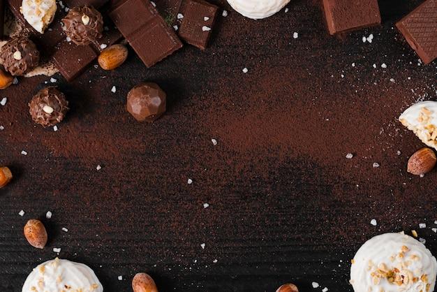 Flat lay dulces de chocolate se mezclan sobre fondo rosa con espacio de copia