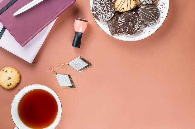 Flat lay home escritorio de oficina. espacio de trabajo femenino con agenda, flores, dulces, accesorios de moda. concepto de blogger de moda.