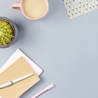 Flat lay home escritorio de oficina. espacio de trabajo femenino con cuaderno, anteojos, taza de té, diario, planta. copia espacio