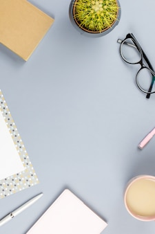 Flat lay home escritorio de oficina. espacio de trabajo femenino con planificador, anteojos, taza de té, diario, planta. copia espacio