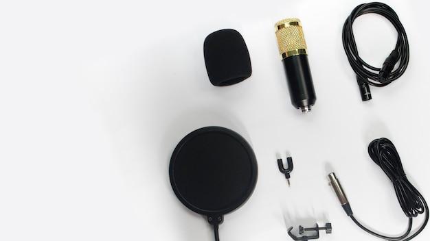 Flat lay limpio blanco negro para su sitio web o proyecto con micrófono portátil
