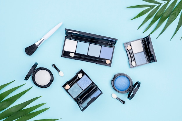 Flat lay pack de productos de belleza sobre fondo azul.