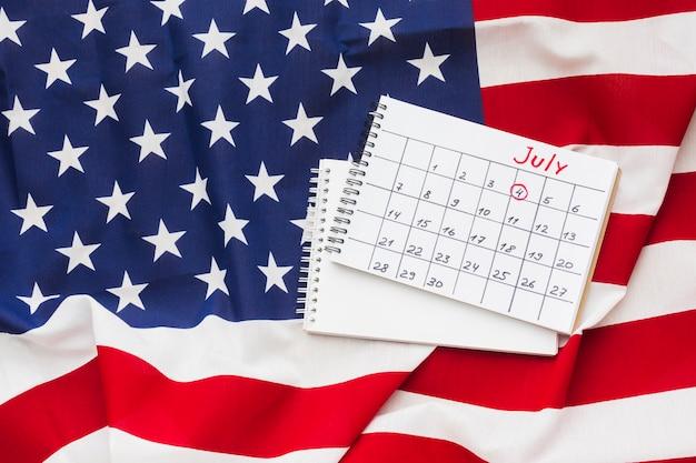 Flat lay pf julio mes calendario en la parte superior de la bandera americana