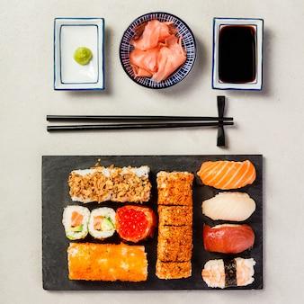 Flat-lay de sushi en fondo de hormigón gris, composición cuadrada