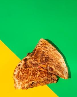 Flat lay tortilla crujiente pan sobre fondo verde y amarillo