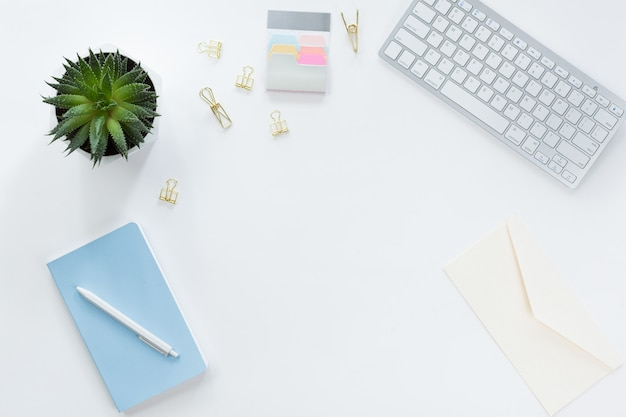 Flat lay, vista superior escritorio mesa de oficina. espacio de trabajo con pincel, computadora portátil, ramo de flores de color lila, carrete con cinta beige y azul, diario de menta sobre fondo blanco.